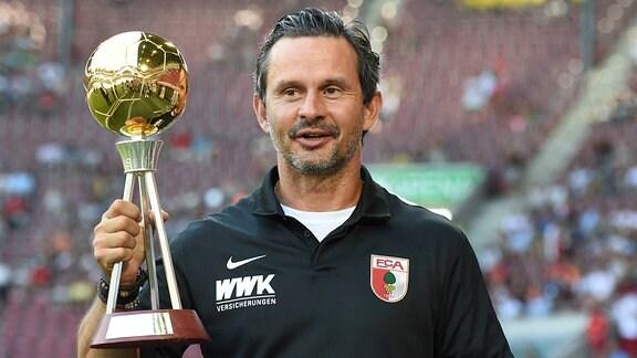 Dirk Schuster, Trainer des Fussball-Bundesligisten FC Augsburg 1907, posiert mit dem Kicker-Pokal Trainer des Jahres der Saison 2015/16