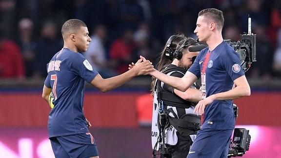 Zwei Fußballer geben sich im Stadion die Hand.