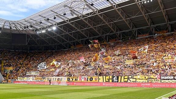 Fans mit wehenden Fahnen im voll besetzter K-Block im Dynamo-Stadion.