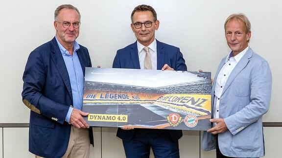 Karl-Heinz Rummenigge, Michael Born und Jens Heinighalten ein Plakat mit einer Stadionaufnahme in denn Händen.