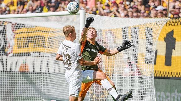 Dynamo Dresdens Torwart Kevin Broll (rechts) schlägt den Ball vor Waldemar Sobota davon.