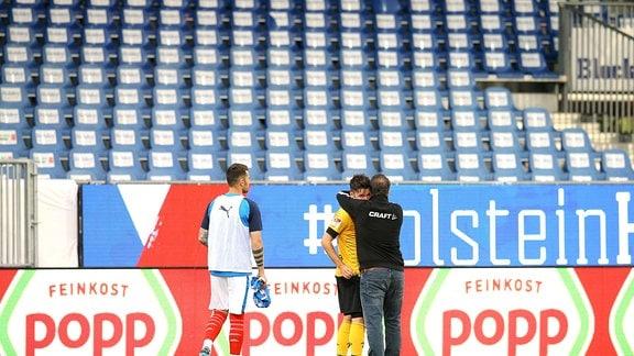 am Boden zerstört ist nach dem Schlusspfiff der Dresdner Spieler Niklas Kreuzer hier umarmt von Trainer Kauczinski
