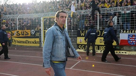 Sportdirektor Ralf Minge läuft vör der Fantribüne durchs Stadion, 2009