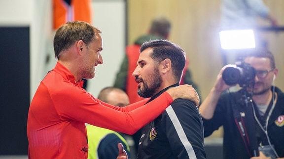 PSG-Trainer Thomas Tuchel (links) und Dresdens Cheftrainer Cristian Fiel begegnen sich im Spielertunnel und begrüßen sich herzlich, DynamoTV-Filmemacher Steffen Kuttner (rechts hinten) fängt die Szene ein.