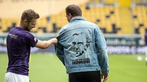 Dynamos Spieler tragen vor dem Erwärmen Jeansjacken mit dem Bild Ralf Minges und den Worten - DANKE FÜR ALLES MINGUS!