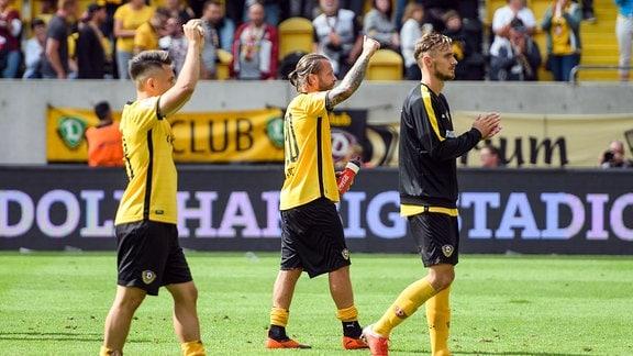Dresdens Patrick Ebert (Mitte), Baris Atik (links) und Linus Wahlqvist (rechts) bedanken sich nach Abpfiff bei den Fans