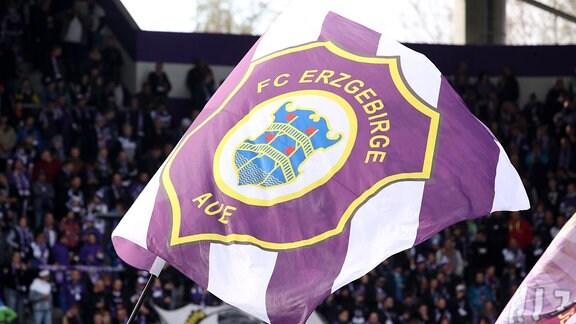 Fans von Erzgebirge Aue schwenken Fahne mit Logo