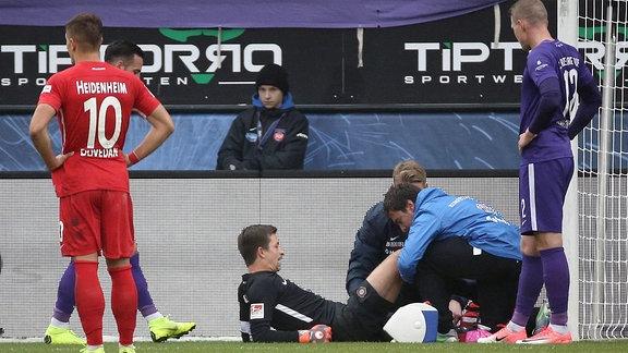 Martin Männel (FC Erzgebirge Aue) verletzt, ein Arzt untersucht ihn.