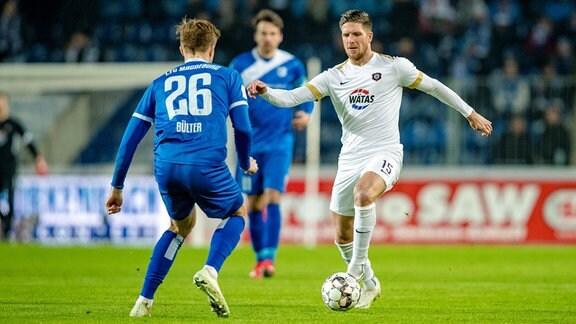 Dennis Kempe 15, FC Erzgebirge Aue, im Duell mit Marius Bülter 26, 1. FC Magdeburg.