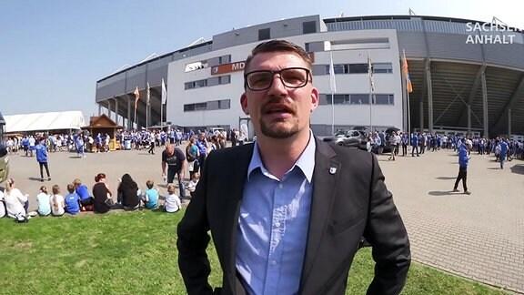 Ein Mann steht vor einem Fußballstadion.