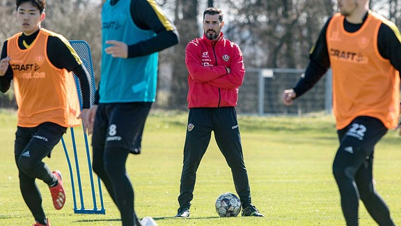 Cheftrainer Cristian Fiel schaut seinen Spielern bei der Übung zu.