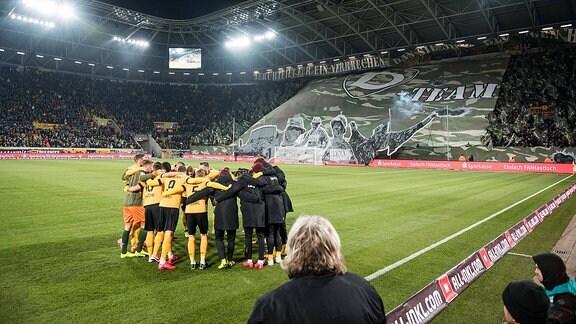 Mannschaftskreis der Dynamo-Spieler, im Hintergrund eine Choreographie im K-Block