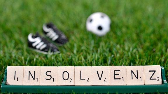 Das Wort Insolvenz, dahinter Fußballschuhe und ein Ball