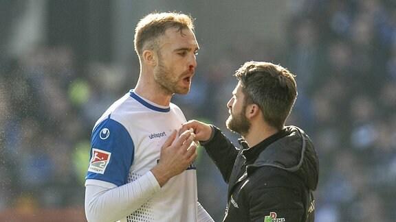 Magdeburgs Jan Kirchhoff wird an der blutenden Nase behandelt.