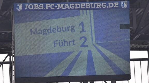 Das Logo der 1. FC Magdeburg und der Spielstand auf der Leinwand.