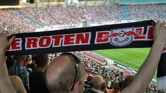 Fan von RB Leipzig hält einen Fanschal hoch.
