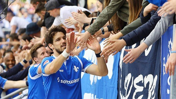 Romain Bregerie (SV Darmstadt 98) klatscht mit den Fans ab.