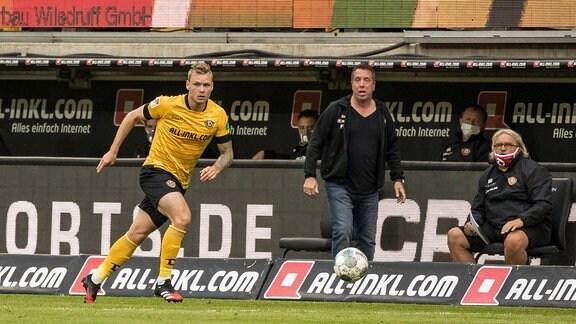 Dresdens Brian Hamalainen links am Ball, im Hintergrund Cheftrainer Markus Kauczinski Mitte und sein Co-Trainer Heiko Scholz rechts.