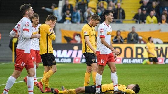 Kurz nach Abpfiff: Dresdens Jannis Nikolaou liegt am Boden, Lucas Röser blickt auf ihn herab, Jannik Müller schlägt die Hände ins Gesicht
