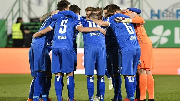 Die Mannschaft des 1. FC Magdeburg bildet einen Teamkreis.