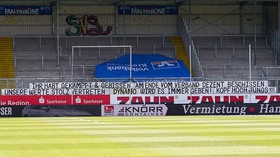 er leere Gästefanblock von SG Dynamo Dresden zeigt einen Banner mit der Aufschrift: Ihr habt gekämpft und gebissen. Am Ende vom Verband dezent beschissen. Unsere Werte stolz vertreten. Dynamo wird es immer geben. Kopf hoch, Jungs