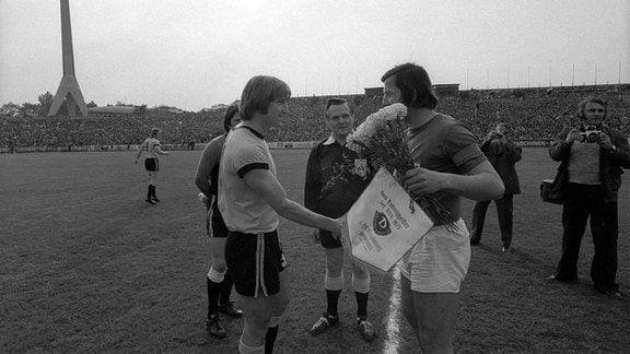 Hans Jürgen Dörner (li., Dynamo Dresden) gratuliert Manfred Zapf (re., Magdeburg) vor Spielbeginn mit Blumen und Wimpel zum Meistertitel 1975