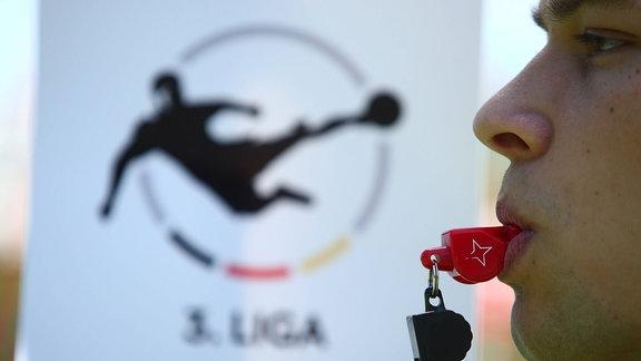 Schiedsrichter pfeift vor dem Logo der 3. Liga.