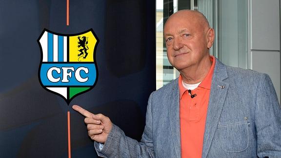 Lutz Lindemann zeigt auf das Vereinslogo des Chemnitzer FC