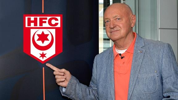 Lutz Lindemann zeigt auf das Vereinslogo von Hallescher FC