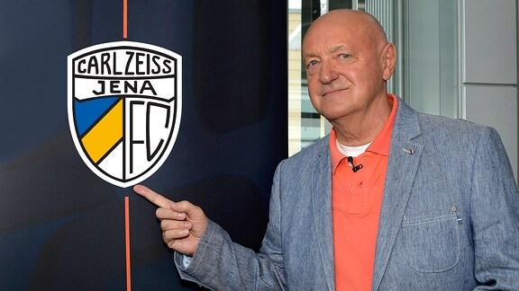 Lutz Lindemann zeigt auf das Vereinslogo von FC Carl Zeiss Jena