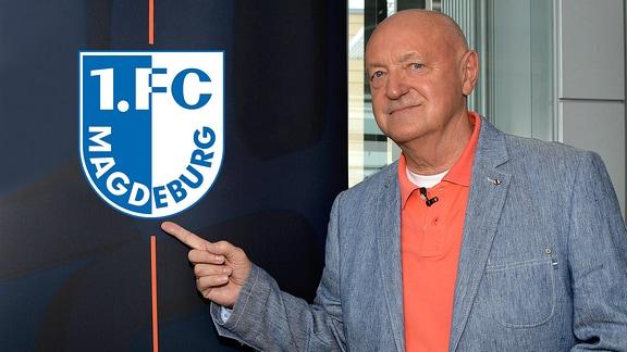 Lutz Lindemann zeigt auf das Vereinslogo von 1. FC Magdeburg