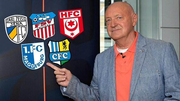 Lutz Lindemann zeigt auf die Vereinslogos der dritten Liga: FC Carl Zeiss Jena, FSV Zwickau, Hallescher FC, 1. FC Magdeburg und Chemnitzer FC