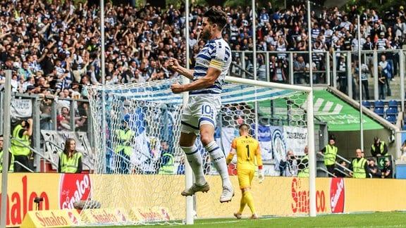 Jubelnder, in die Luft springender Fußballer mit geballter Faust.