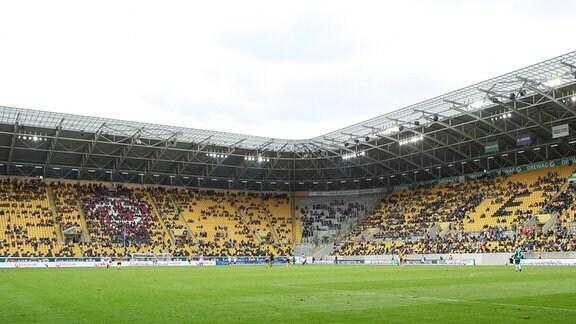 Zuschauer mit Abstand und Maske im Stadion
