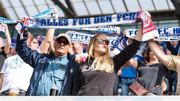 Fans des Hansa Rostock halten Schals in die Luft.