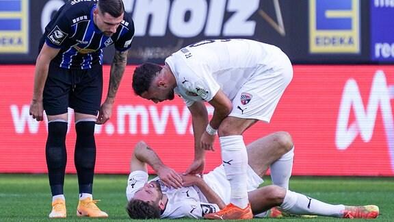 Marcel Hofrath und Fatih Kaya kümmern sich um den verletzten Rico Preißinger.