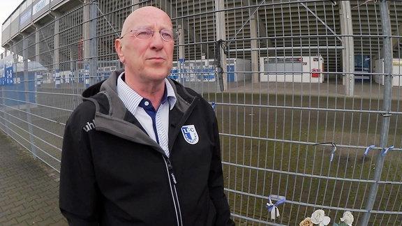 Ein Mann steht vor einem Fußballstadion