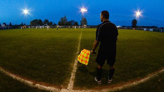 Drei Flutlichtmasten und Schiedsrichter-Assistent Marko Gassmann (vorn) beim Landespokalspiel Großengottern vs. Jena (06.09.2019)