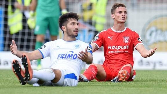 Zwei Fußballer sitzen auf dem Rasen und heben fragend die Arme.