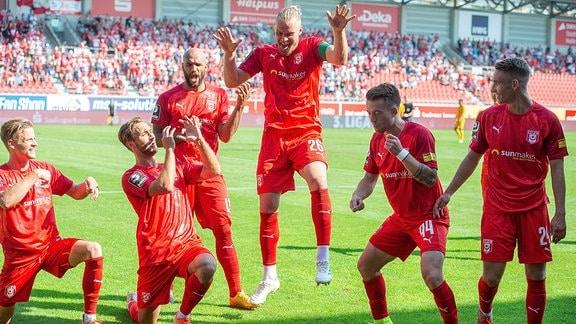 Eine Fußball-Mannschaft feiert einen Fußballer nach einem Tor.