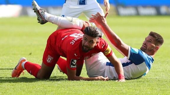 Kai Bruenker Brünker (1. FC Magdeburg,9) und Antonios Papadopoulos (Hallescher FC Halle) liegen auf dem Rasen.