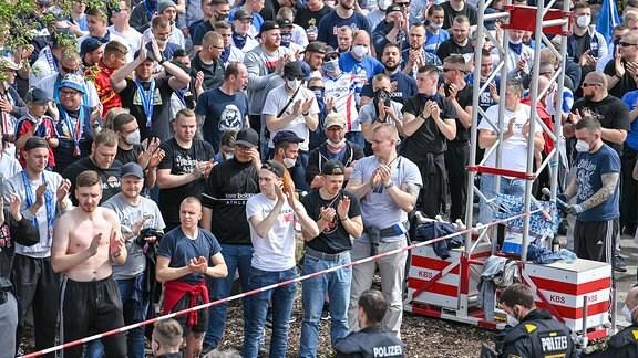 viele Fans des FC Hansa Rostock stehen vorm Stadion uind feuern die Mannschaft an.