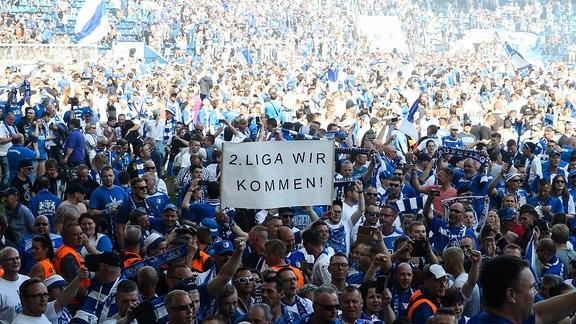 Fans vom 1. FC Magdeburg feiern im Innenraum mit Plakat '2. Liga wir kommen'