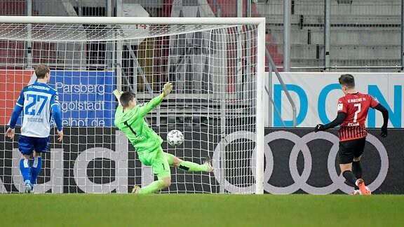Dennis Eckert Ayensa (FC Ingolstadt) erziehlt das Tor zum 1:0. Morten Behrens (1.FC Magdeburg) kann nicht halten