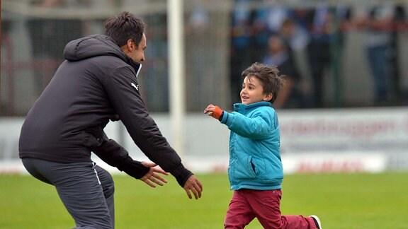 Ismail Atalan (Trainer VfL Sportfreunde Lotte 1929) freut sich nach dem Abpiff mit einem Kind