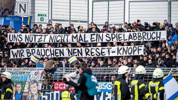 Die Fans des FC Carl Zeiss Jena mit einem Banner mit der Aufschrift «Uns nützt nicht mal ein Spielabbruch Wir brauchen nen Reset-Knopf» im 3. Liga Spiel des FC Carl Zeiss Jena gegen den TSV 1860 München.