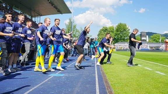 Nach Spielschluss: Trainer Lukas Kwasniok (Jena, rechts) streift sich als letzter das Siegertrikot über, links sein erleichtertes Team