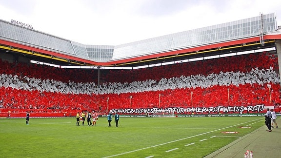 Fußballer im Stadion, die Tribünen sind rot und weiß beflaggt.