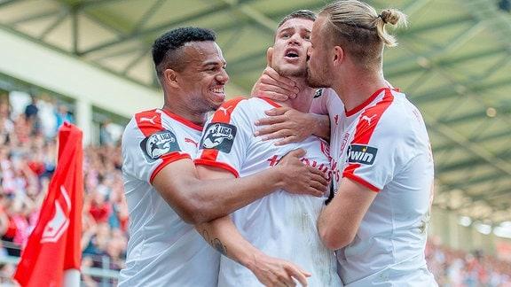 Die drei Torschützen unter sich. Marvin Ajani (HFC) und Sebastian Mai (HFC) freuen sich mit Kilian Pagliuca (HFC) im Spiel des HFC Hallescher FC vs. TSV 1860 München.