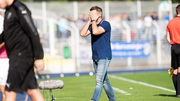 Trainer Lukas Kwasniok (Jena) schlägt die Hände vor dem Gesicht zusammen.
